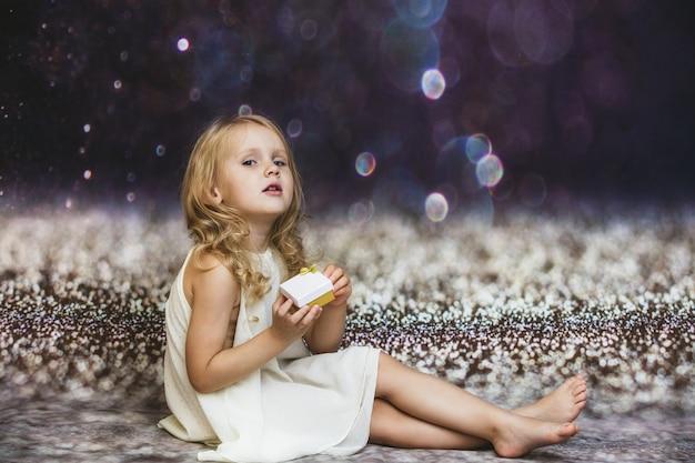 Bambina carina e bella sullo sfondo con un bagliore nella confezione regalo in mano