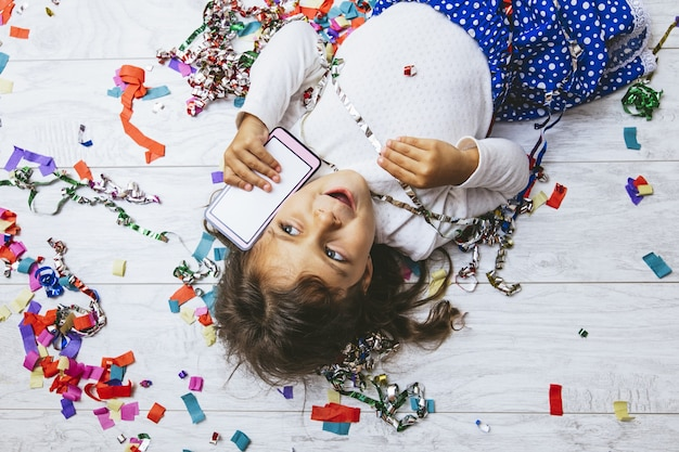 Bambina carina e bellissima con coriandoli multicolori sul pavimento con un telefono cellulare
