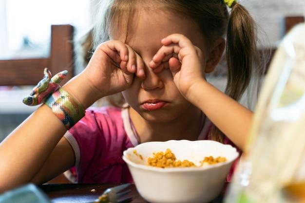 La bambina mangia a casa in cucina e capriccio