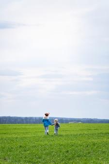 Bambina bambina e madre donna corrono e saltano, erba verde nel campo, tempo primaverile soleggiato, sorriso e gioia del bambino, cielo blu con nuvole