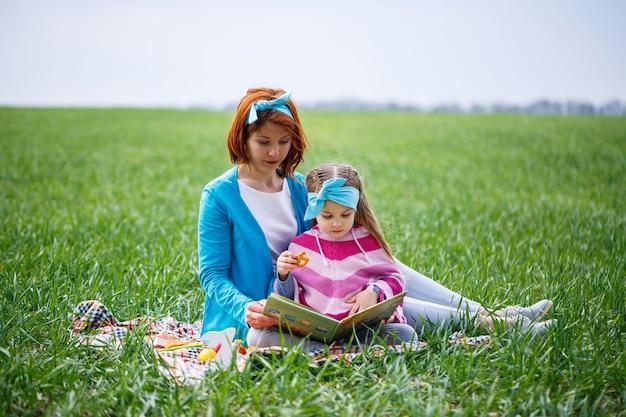 Bambina bambina e madre donna si siedono sul copriletto e leggono un libro con una fiaba, erba verde nel campo, tempo soleggiato primaverile, sorriso e gioia del bambino, cielo azzurro con nuvole
