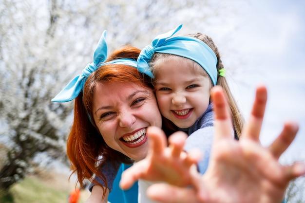 Bambina bambino e madre donna cammina attraverso la foresta primaverile con alberi in fiore, ridere e giocare, l'inizio della primavera, le vacanze in famiglia, l'amore dei genitori
