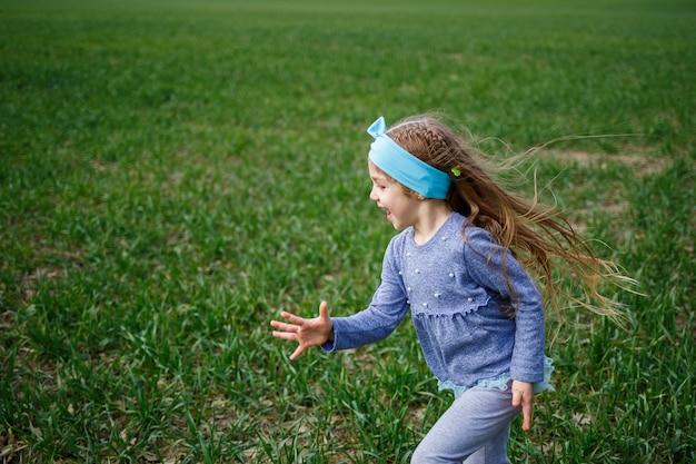 La bambina corre su erba verde nel campo, tempo primaverile soleggiato, sorriso e gioia del bambino, cielo blu con nuvole