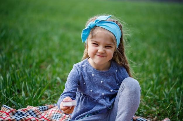 La bambina si siede sul copriletto e mangia biscotti e marmellata, erba verde nel campo, tempo primaverile soleggiato, sorriso e gioia del bambino, cielo blu con nuvole