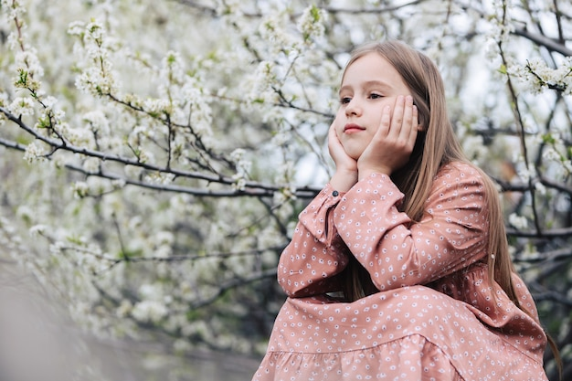 Una bambina si siede in giardino sotto un albero in fiore, poggia la testa sulle mani e guarda in lontananza con uno sguardo pensieroso.