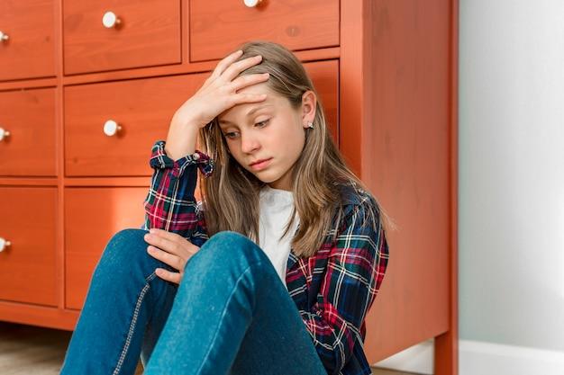 Una bambina si siede tristemente con le gambe piegate sul pavimento salute mentale