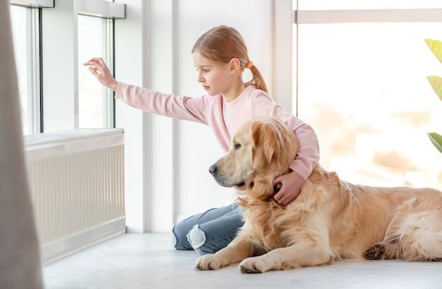 Bambina con il cane golden retriever seduto sul pavimento e guardando fuori dalla finestra