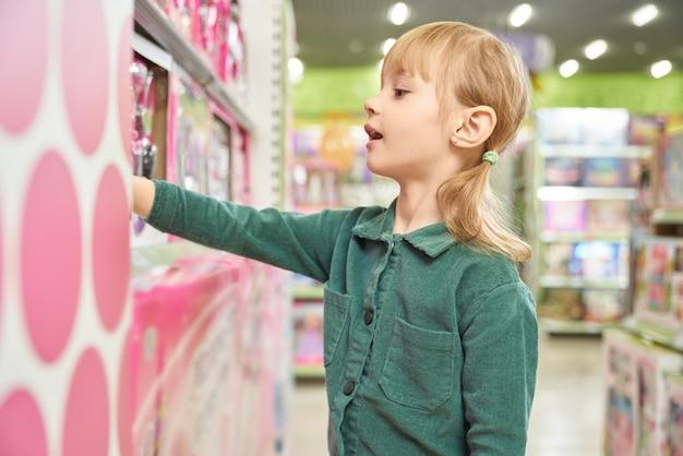 Bambina che sceglie giocattolo nel grande centro commerciale.