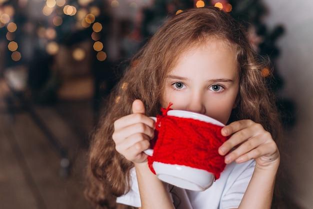 Bambina nella decorazione di natale con tè a casa accogliente con le luci variopinte del nuovo anno