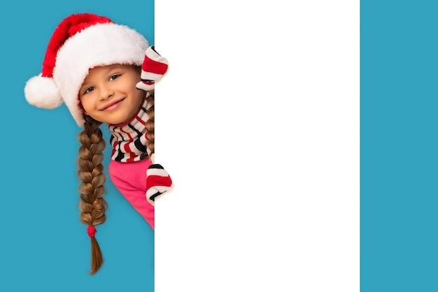 Una bambina in un cappello di natale e guanti guarda da dietro uno sfondo bianco.