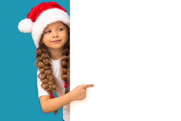 Una bambina con un cappello di natale indica il tuo annuncio