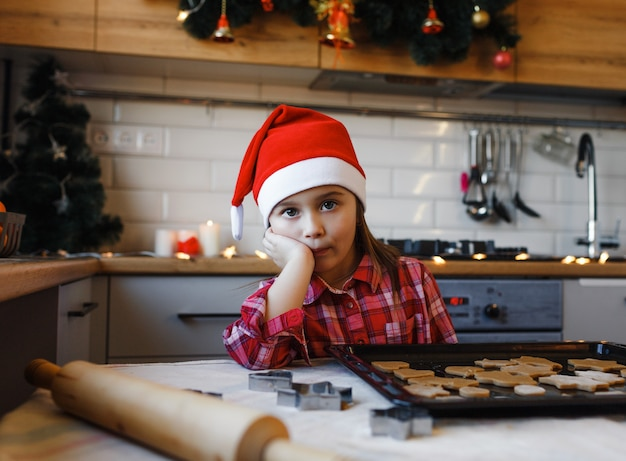 Bambina con un cappello di natale, triste in cucina vicino a un vassoio di biscotti