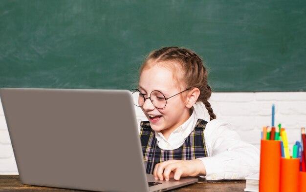 Bambina in aula su un computer portatile