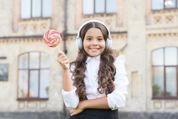 La bambina in uniforme di classe mangia lecca-lecca. di nuovo a scuola. educazione moderna con le nuove tecnologie. bambino al cortile della scuola. immagina che sia cantante. il bambino ha una pausa musicale. ragazza in cuffia.