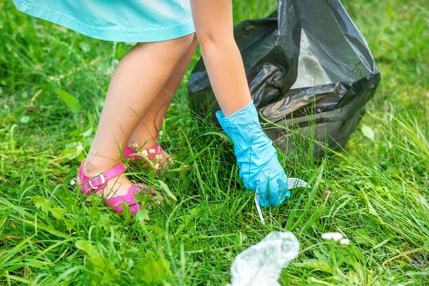 La bambina pulisce la spazzatura di plastica sull'erba verde nel parco