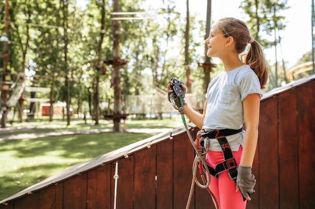 Scalatore della bambina nel parco avventura, parco giochi. bambino che si arrampica sul ponte sospeso