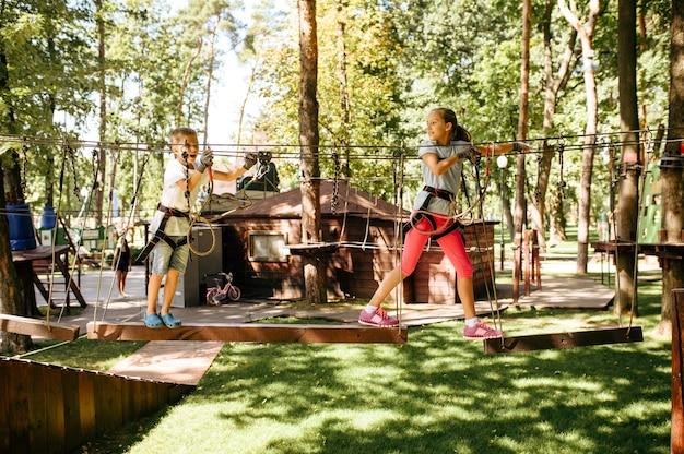 La bambina si arrampica nel parco delle funi. bambino che si arrampica sul ponte sospeso