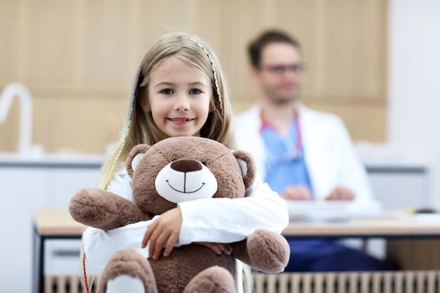 Bambina in clinica con pediatra in background