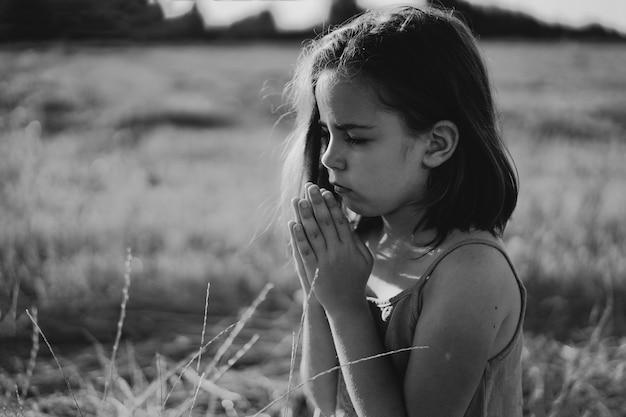 La bambina chiuse gli occhi, pregando in un campo.