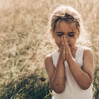 La bambina chiuse gli occhi, pregando all'aperto, le mani giunte nel concetto di preghiera per fede, spiritualità e religione. pace, speranza, concetto di sogni.