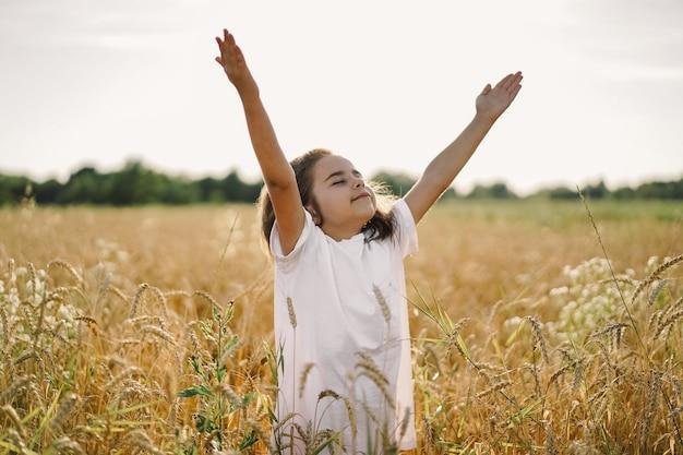 La bambina ha chiuso gli occhi e ha alzato le mani al cielo, pregando in un campo di grano. concetto di religione