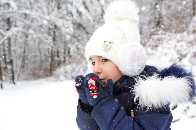 Una bambina al freddo si riscalda le mani con i guanti, respira aria calda dalla bocca sulle mani. vacanze invernali