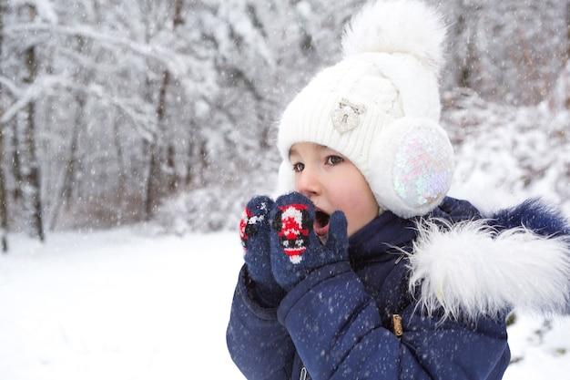 Una bambina al freddo si riscalda le mani con i guanti, respira aria calda dalla bocca sulle mani.