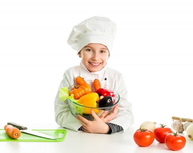 Bambina-cucinare dalla tavola con le verdure