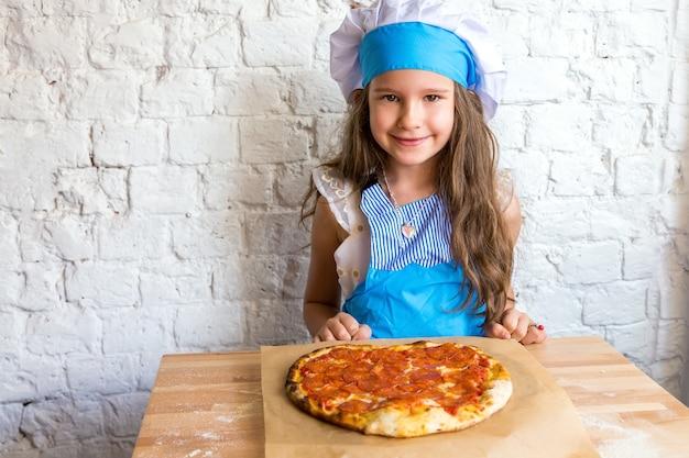 Cuoco della bambina che sorride vicino alla pizza ai peperoni a forma di cuore dopo la preparazione.