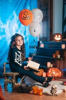 Bambina in un costume di scheletro che tiene palloncini