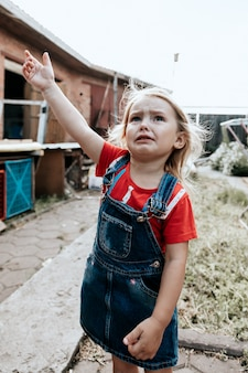 La bambina piange in cortile in una giornata calda