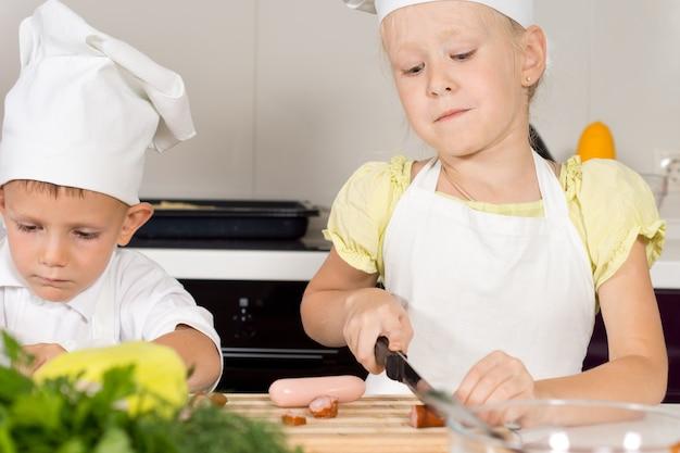 Bambina che taglia gli ingredienti per la pizza fatta in casa
