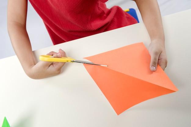 Bambina che taglia una carta isolata su sfondo bianco