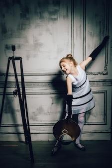 Bambina che balla con lampada da terra in un abito vintage. bambino in un elegante abito glamour e guanti. ragazza retrò, modella, bellezza. moda e bellezza, stile pinup, infanzia.