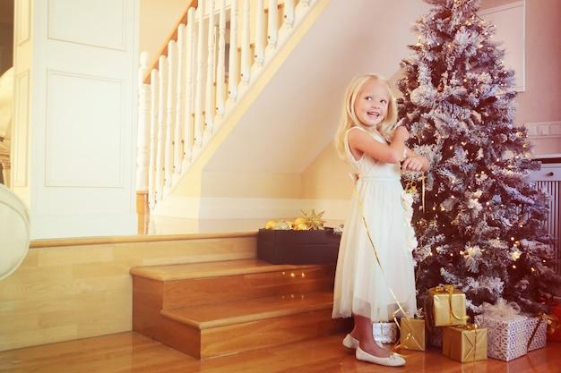 Bambina che decora l'albero di natale a casa