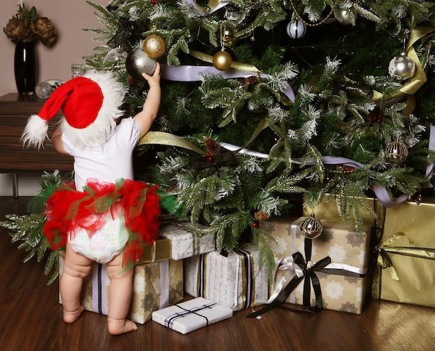 Bambina che decora un albero di natale giocattoli, vacanze, regali, dec