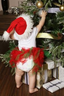 Bambina che decora un albero di natale con le palle