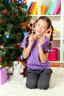 Bambina che decora l'albero di natale