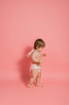 Bambina in un pannolino e con ali d'angelo su un muro rosa