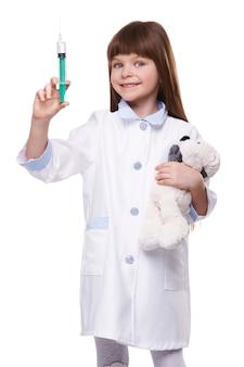 Medico della bambina in cappotto medico che tiene la siringa e l'orso del giocattolo sulla parete isolata bianca