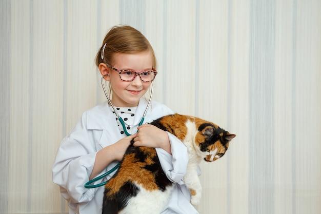 Bambina in cappotto di un medico sorride e invita per il trattamento. il paziente è un gatto domestico.
