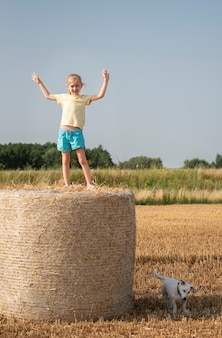Bambina e cane che si divertono in un campo di grano in una giornata estiva. bambino che gioca al campo di balle di fieno durante il periodo del raccolto.