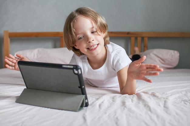 Bambina che fa i compiti online sdraiata sul letto a casa comunicazione con i parenti online
