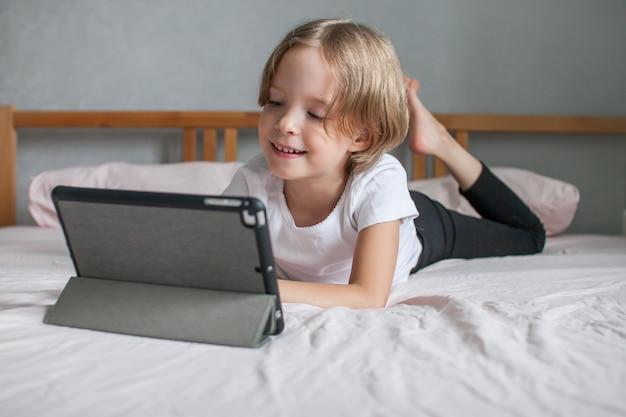 Bambina che fa i compiti online sdraiata sul letto a casa comunicazione con i parenti online il