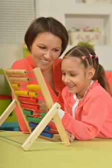 Bambina che fa esercizi di matematica con sua madre a casa