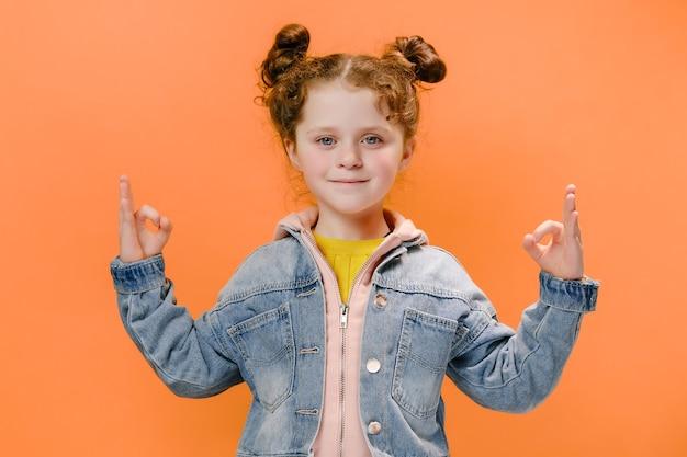 Bambina che fa segni ok su sfondo arancione