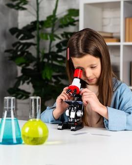 Bambina facendo esperimenti scientifici e guardando attraverso il microscopio