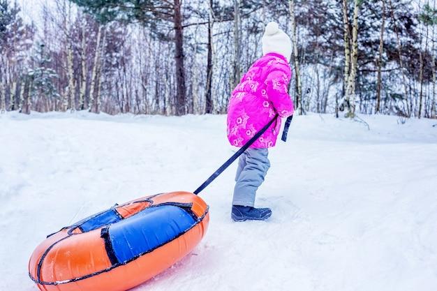La bambina trascina la cheesecake su una collina innevata. concetto di attività invernali all'aperto per bambini.