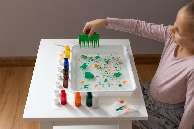Bambina che disegna nella tecnica ebru. ebru art