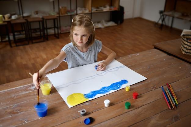 Bambina disegno con pennello e vernici al tavolo, vista dall'alto, bambino in officina. lezione al liceo artistico. giovane pittore, piacevole hobby, infanzia felice
